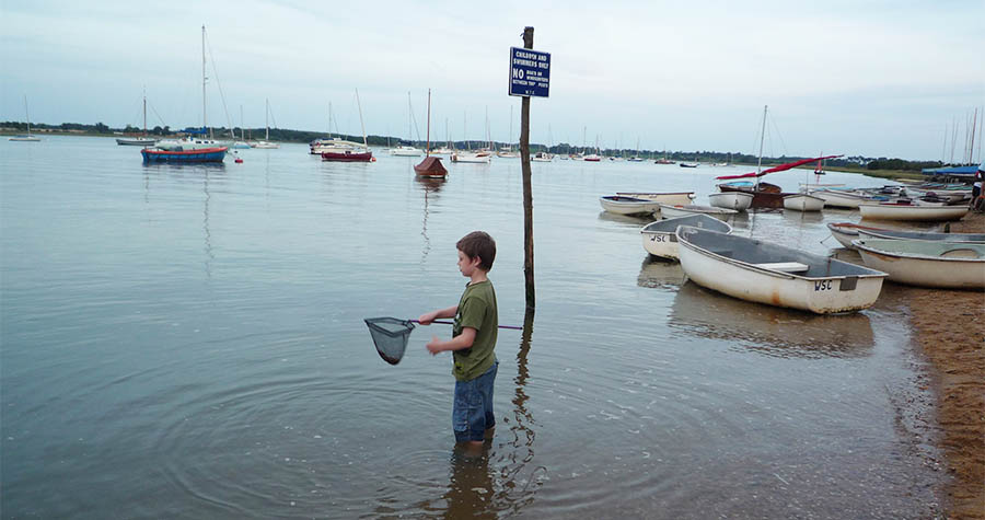Child with a net at River Deben in Suffolk